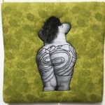 Multimedia. Photograph of a large bodied light skinned woman is photographed from the back. On her buttocks and legs are stenciled 30,000 year old goddess images in embroidery. She is mounted on a puffy green textured background. Piece is 12 inches square.
