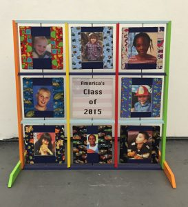 """Front of the Witness sculpture. 12 large 12"""" squares are on a brightly colored frame. Nine different 12"""" square pivots on a vertical axis (similar to a tic-tac-toe board). On the front side, all squares except the center square have a photos of children who range in age from 2-16. Each photo is surrounded by brightly colored fabrics. The center square reads: America's Class of 2015 with a faint image of an American flag behind the words."""